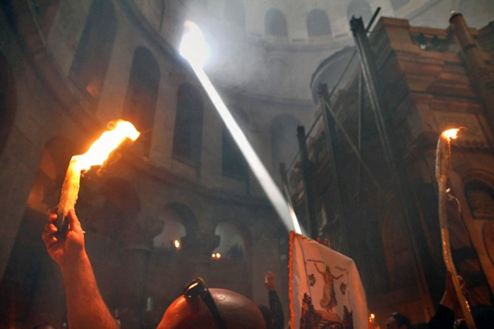 epa02699556 An Eastern Orthodox Christian with his burning candles during the miracle of the Holy Fire as a shaft of light enters the rotunda and he passes the Tomb of Christ (R) in the Church of the Holy Sepulchre in Jerusalem on 23 April 2011, the day before Easter. The fire comes forth from a hole in the Tomb of Christ and quickly spreads among the faithful in the church and then outside through Jerusalem and even to foreign countries. The miracle is recorded as happening each year since 1106 and is considered by believers to be the flame of the Resurrection power, as well as the fire of the Burning Bush of Mount Sinai.  EPA/JIM HOLLANDER